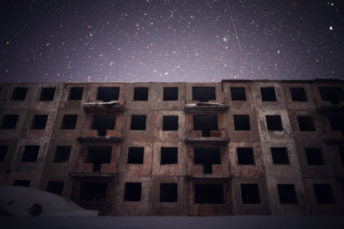 Starlight illuminates abandoned structures, built to test the impact of nuclear explosions.