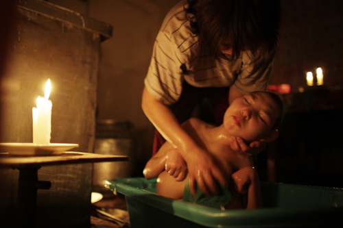 Mayra Zhumageldina bathes her daughter, Zhannoor, sixteen, who was born with microcephalia..