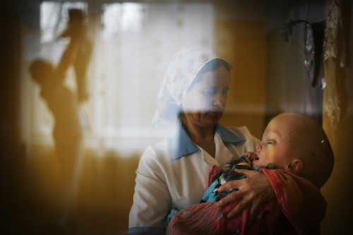 Nurse Larissa Soboleva holds two-year-old Adil Zhilyaev at an orphanage in Semey.