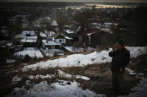 Berik Syzdykov smokes a cigarette on a hill overlooking his hometown of Semey.