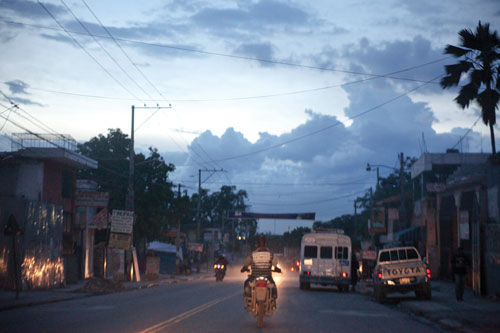 A city street at dusk with motorcycles on the roadway and several vehicles parked off the the right hand side.