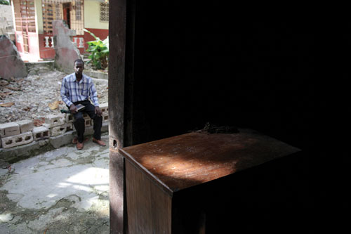 The camera peers out from inside a building with a weathered wooden dresser to the street outside where a Hatian man in a plaid shirt and dress pants sits on a cinderblock wall.
