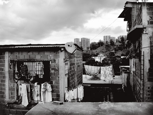 From her self-built house, erected on vacant public land, squatter Anayibe Sánchez has a view of the Valley of Caracas through the tangle of strung-up power lines and laundry hung out to dry.