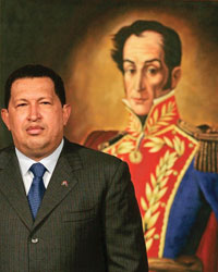 Hugo Chavez standing in front of a painting of a thin man in a red embroidered coat.