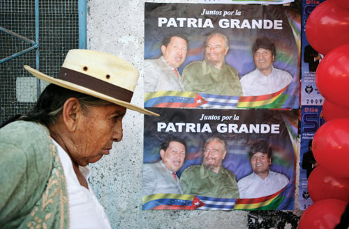 A woman walks past posters depicting Chávez, Bolivian president Evo Morales, and former Cuban president Fidel Castro.