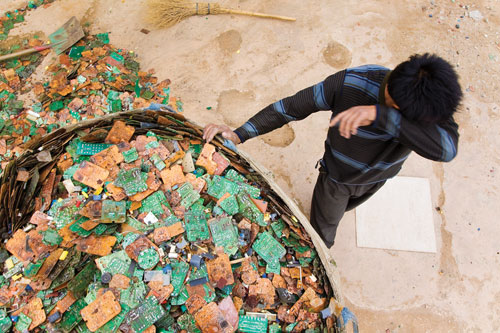 A worker takes a brief break from sorting through stripped circuit boards in Guiyu, China.