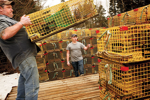 Rick Trundy and son, Nick, load traps onto their trailer.