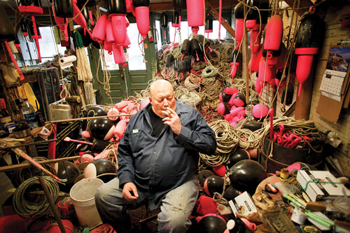 Steve Robbins in his shop, smoking a cigarette, surrounded by ropes and buoys.