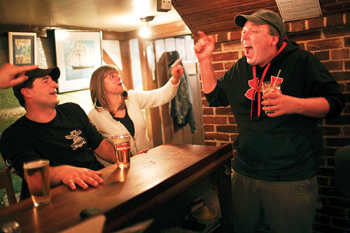Aaron Larrabee takes shelter behind the bar at the Brooklin Pub during an animated discussion with friends.