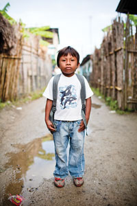 As the dirt paths slowly dry after a rainy season storm, a young Kuna student poses for a portrait on his way home from school.