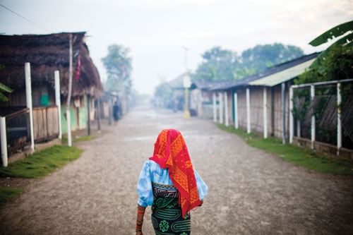 An elderly woman in traditional Kuna dress walks past Usdup island homes as the sun begins to rise.