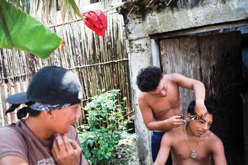 A teenage Kuna boy cuts anothers hair outside a building while a third looks on.