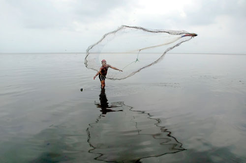 A fisherman casts his net into Lake Xolotlán, despite the risks of illness and disease.