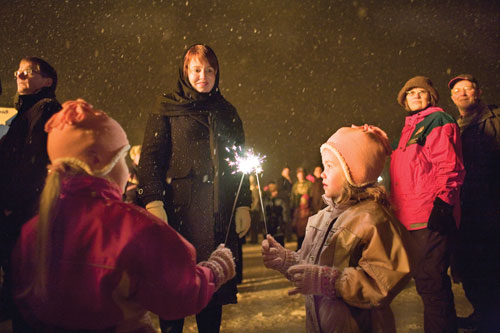 Ingibjörg S. Guðmundsdóttir watches her twin daughters at the annual New Year's bonfire.