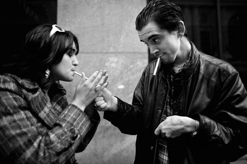 Nick, on the street, in his leather jacket, lighting a cigarette for a girl with dark hair.