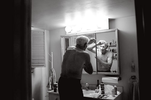 Tom looks at himself in the bathroom mirror while putting on deodorant after a day of working on the farm.