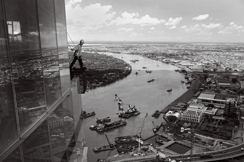 A construction worker looks out from the top of Vietnam's first skyscraper in downtown Saigon.