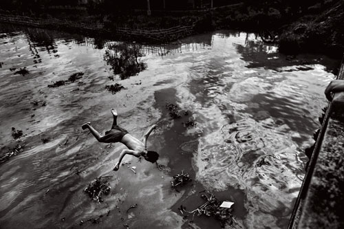 A boy cools off in a polluted tributary of the Mekong River outside of Ho Chi Minh City.
