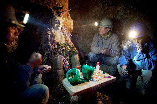 Miners Aurturo Seco, Alejandro Seco, and Milton Seco sit smoking cigarettes around a shrine to El Tio underground inside the mine.
