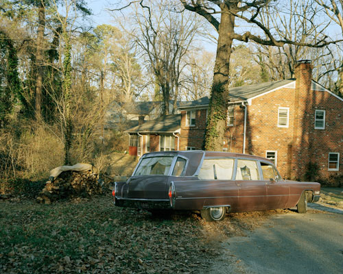 A brown hearse in the author's childhood driveway. The sun is setting and the ground is littered with leaves.