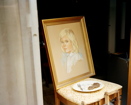 A chair with a painting of the bust of a young girl resting atop it.  On the chair is also a plate of food.