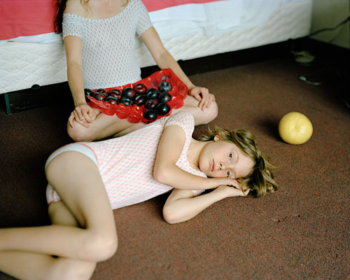 Two young girls in leotards resting on a bedroom floor.  One had several black plums in her lap.