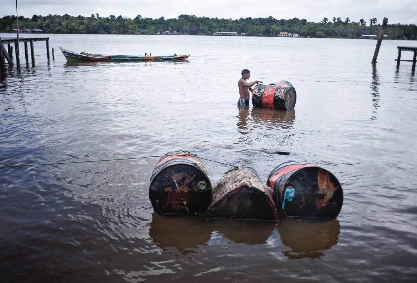 A man hauls oil barrels 