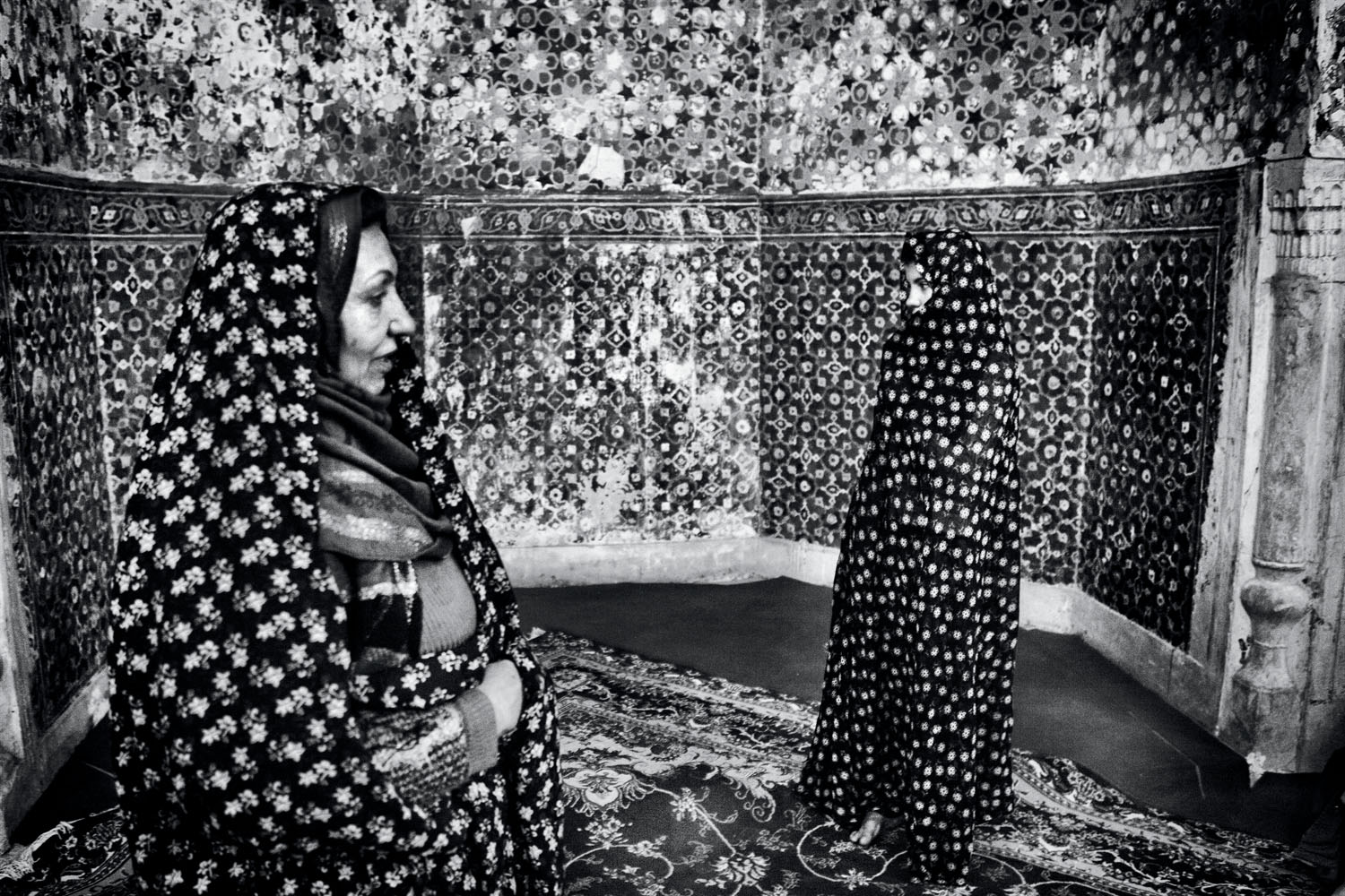 An Afghan woman (left) and her daughter, refugees in Iran, visit a Sufi saint on a trip to their homeland. Afghanistan. 2010. Photo by Monika Bulaj.