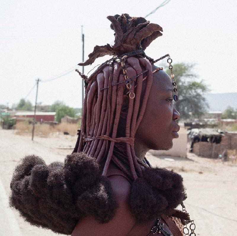 A Himba woman wears ekori, a married woman's headpiece fashioned from cowhide, but the puffed ends of her Remy hair extensions are from China and a plastic cowrie shell dangles like a third eye.