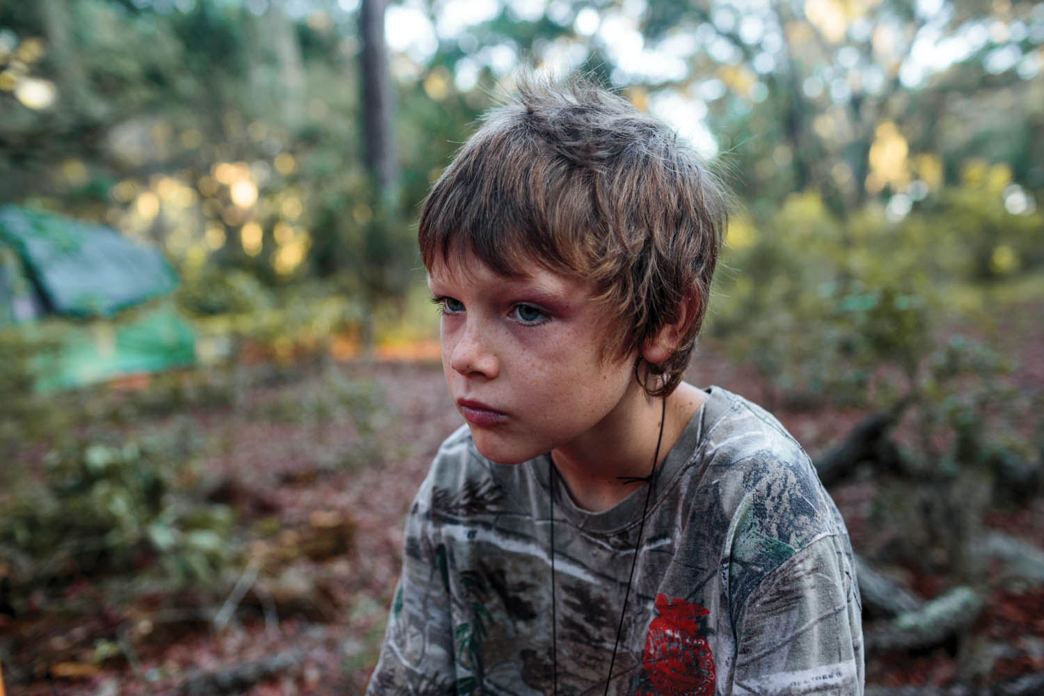 Austin, nine, takes a break from gathering wood for shelter, as part of an exercise at the North Florida Survival School camp, in Florida's Ocala National Forest. The camp's curriculum includes survival-skills training, firearm safety, daily prayer sessions, and hymns. Photographed by Sarah Blesener