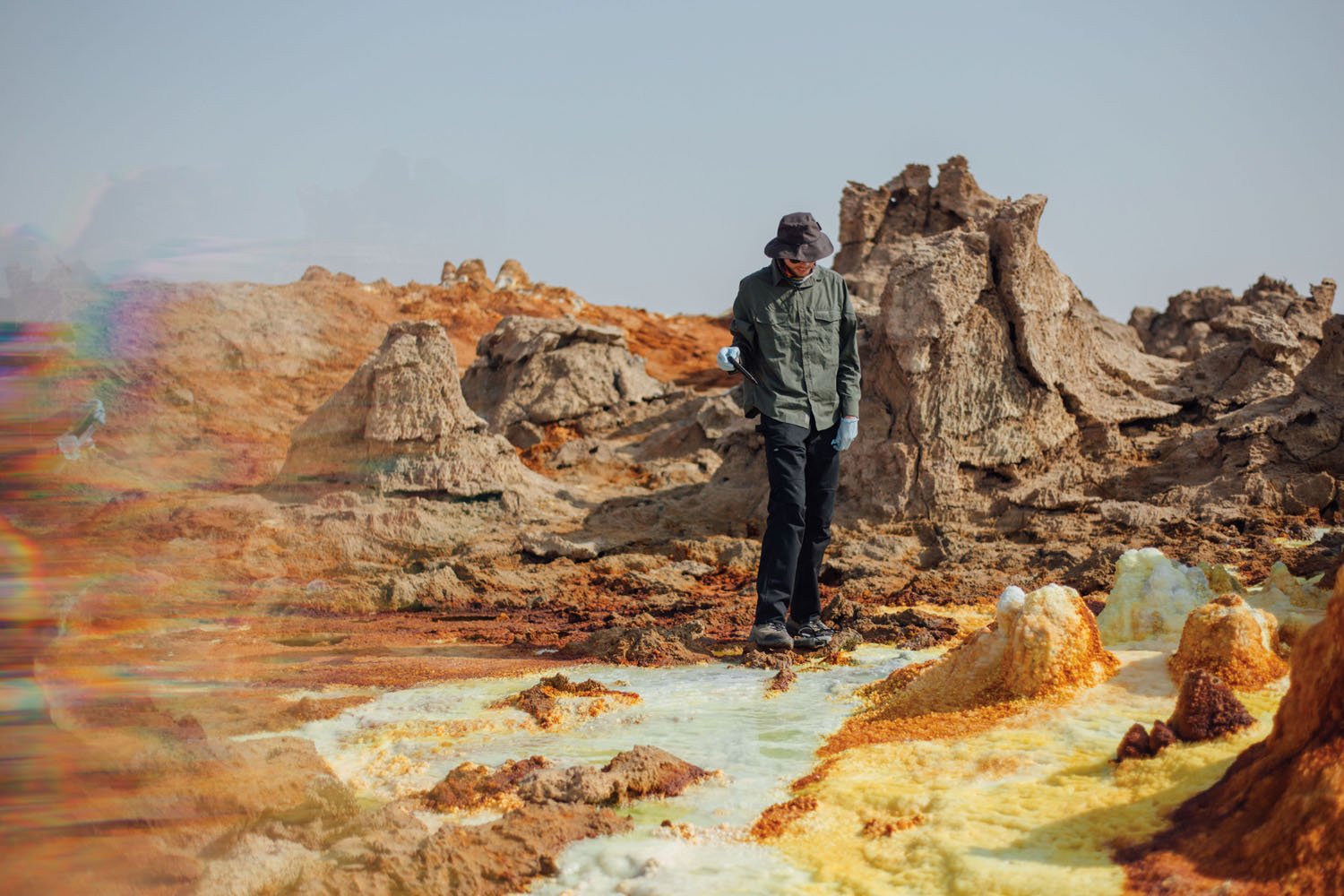 Vincent Rennie prepares to take a pH measurement from a sulfur pool. Photograph by Alex Pritz.