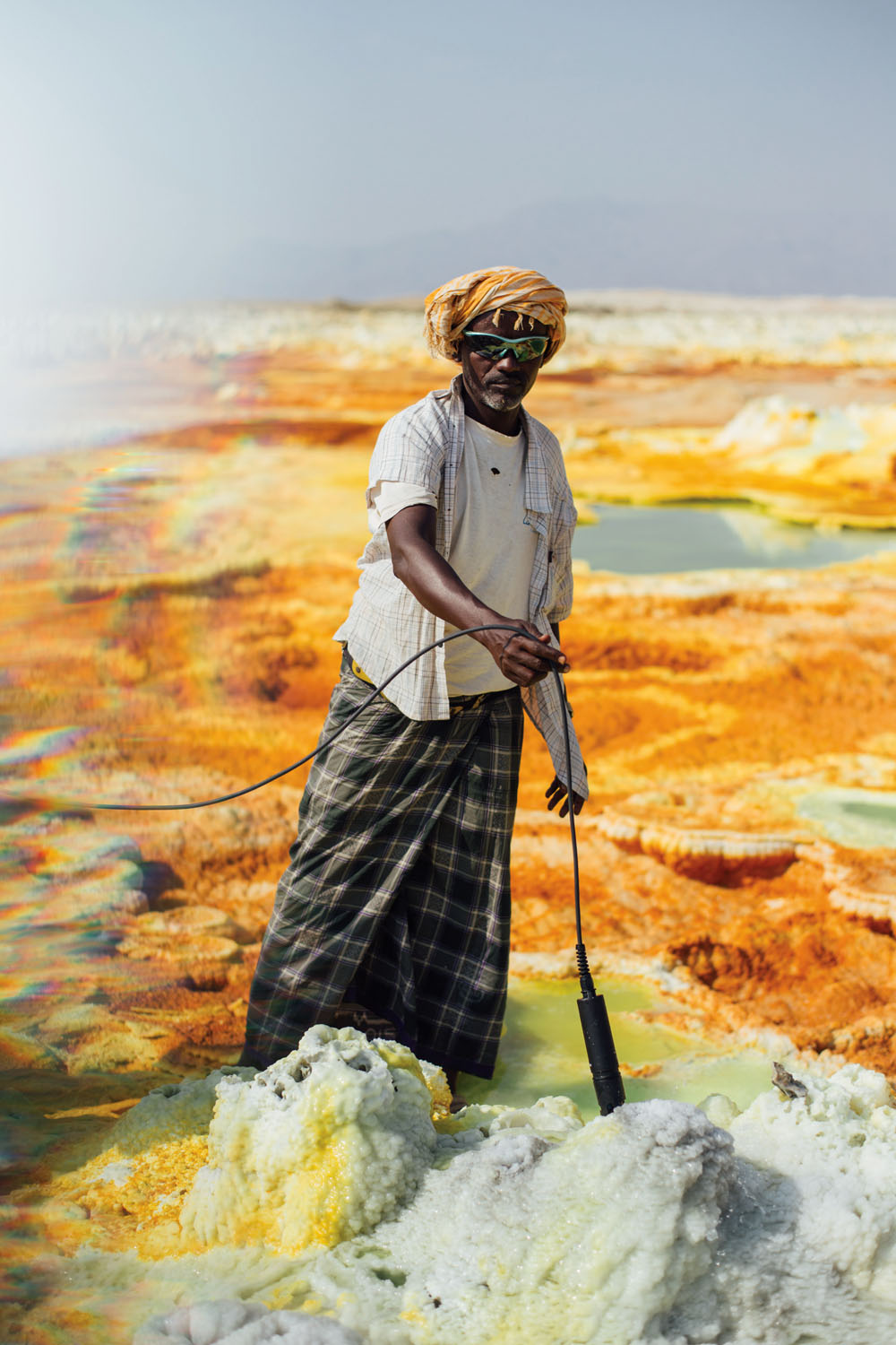 An Ethiopian guide assists with the testing of a sulfur pool. Photograph by Alex Pritz.