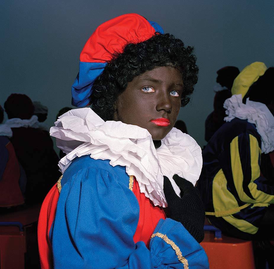 British-born photographer Anna Fox documented the Zwarte Piet tradition in the Netherlands in a series of photographs she took from 1993 to 1998. These two portraits are from her series of eighteen portraits from her book <i>Zwarte Piet</i> (1999).