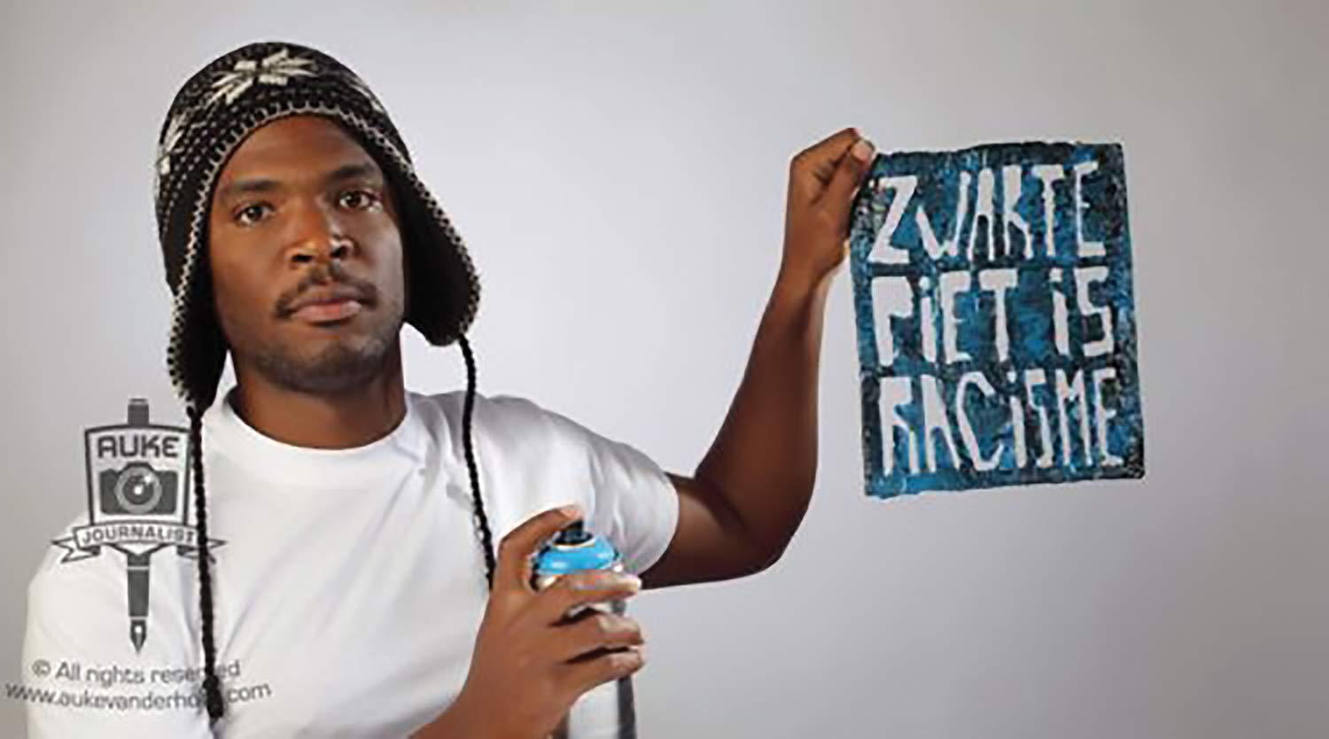 "Student activist Quinsy Gario alongside the logo for the campaign ""Zwarte Piet Is Racisme,"" the Netherlands, November 2011."