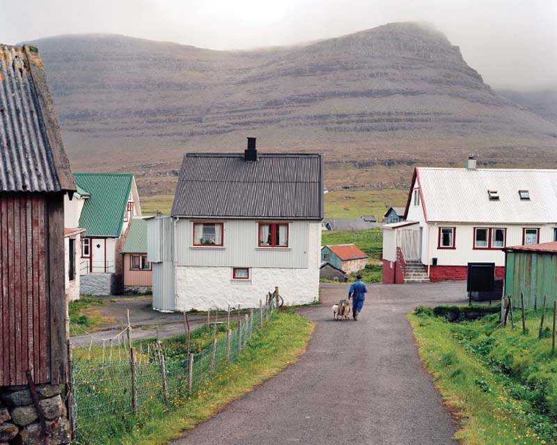 A farmer with his ewe and lamb on the island of Svínoy.
