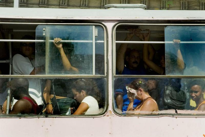 "Cubans baring the heat and crowded buses known as ""camellos."""
