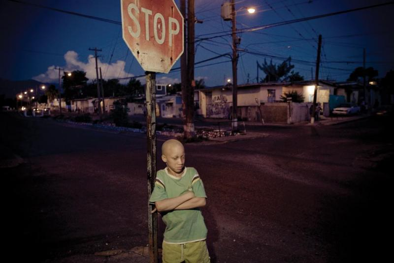 A boy stands at a street corner in Arnett Gardens in Kingston.