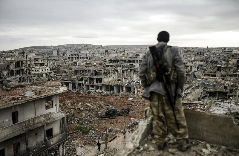 A Kurdish marksman surveying the town of Kobani on January 30, 2015, just days after ISIS militants were driven out. (Bulent Kilic/AFP/Getty images)