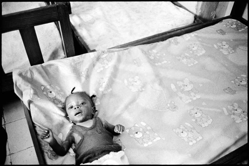 Six-month-old Pierre lies on a bed at the APROSIFA shelter.
