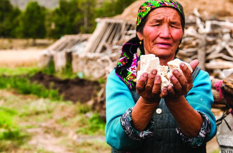 Mapesh, age fifty-seven, with goat cheese. Mapesh was born and raised in Hayndbulaktik, a village the park now intends to raze. (Rebecca Caldwell)