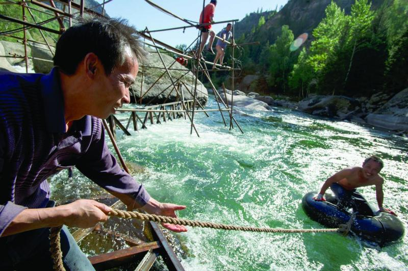 Chinese workers take a break from building a bridge for tourists across the Irytish River.