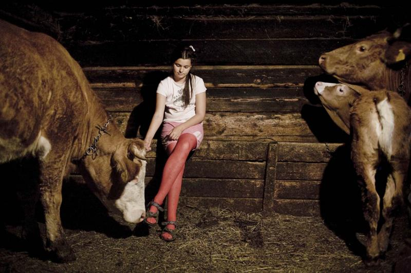 "Eugen David's daughter Diana in the family's barn. The family has ten cows and a few acres of pasture— just enough to get by—but David has refused to sell to the company. ""As long as I have my land, I am the owner of this world,"" he says."