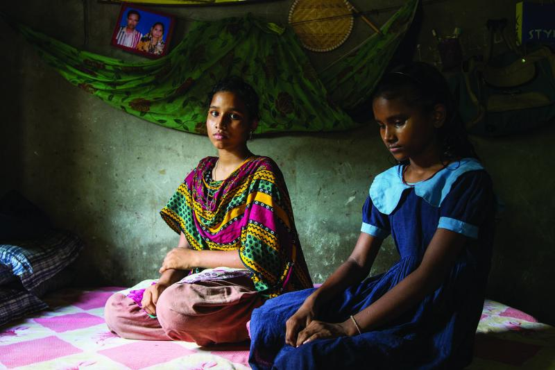 Latifa (left) and Arifa Rahman mourn the loss of their mother, Rina, in their one-room family home in Savar.