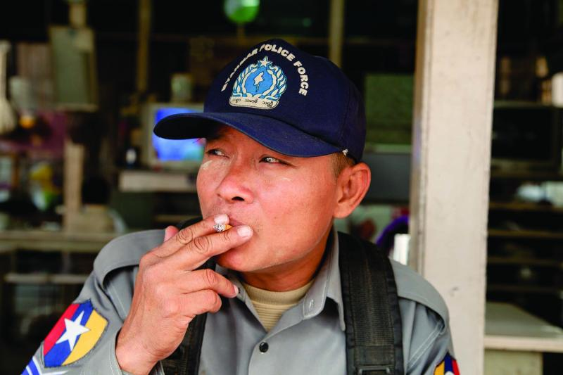 Sergeant Mg Mg Myint takes a drag at a riverside teashop in Tigyaing. The veteran police officer was quick to open his heart, and whiskey, to foreign guests. Photo by Jason Motlagh.