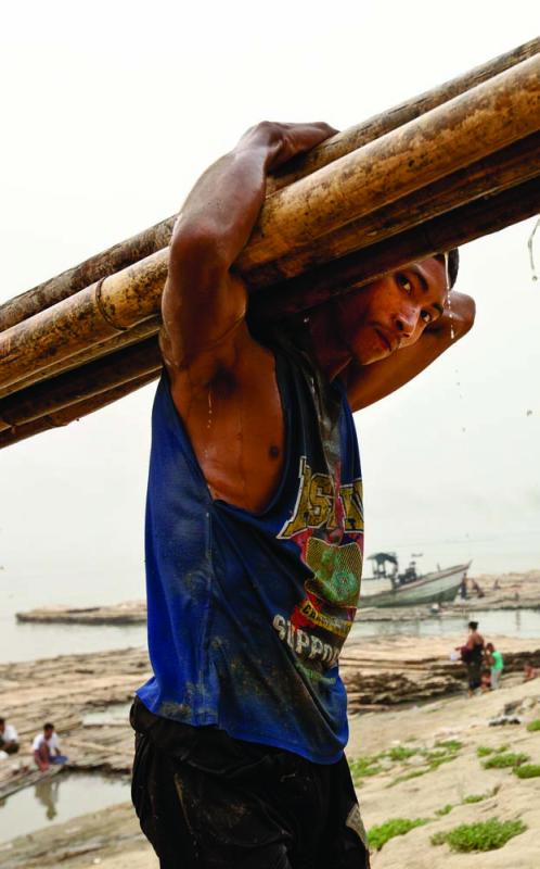 A dockworker bearing bamboo shafts, Mandalay jetty. Photo by Jason Motlagh.