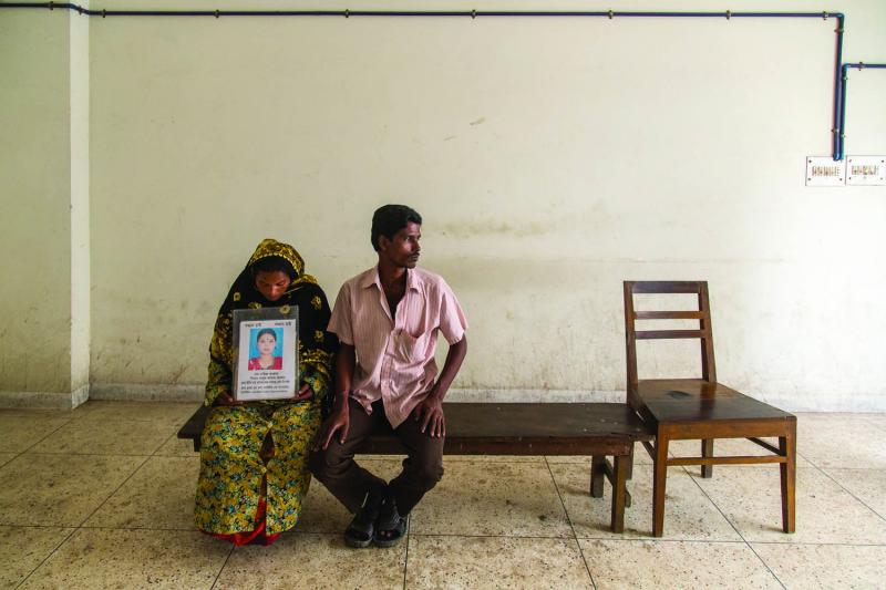 Rashida Begum and her husband, Azad, wait outside the DNA lab in Dhaka in hopes of a positive genetic match confirming their daughter's death.