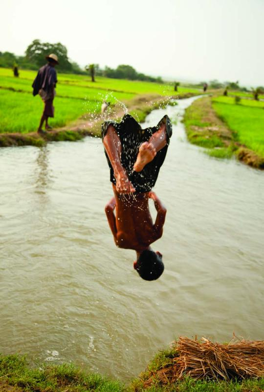 A farm boy takes a splash in an irrigation canal, near Pakokku. The canal networks feed the rice paddies that flourish along the Irrawaddy. Photo by Jason Motlagh.