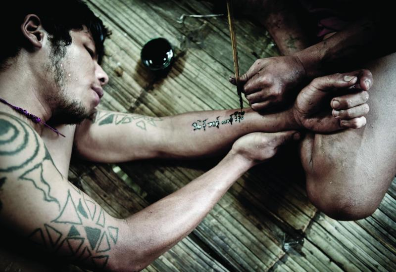 Soldiers at an undisclosed KNLA base tattoo each other using ink and sharpened stick. Many of the Karen believe that certain symbols will act as amulets and protect them in battle.