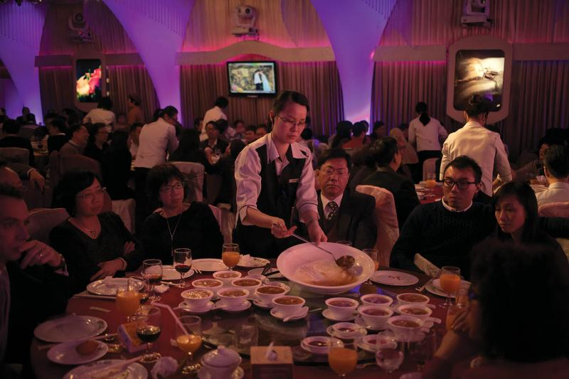 Friends and family are served shark-fin soup at a wedding banquet in Hong Kong. The soup is one of the most important traditional Chinese dishes and is served as a way of showing respect to guests at special occasions.