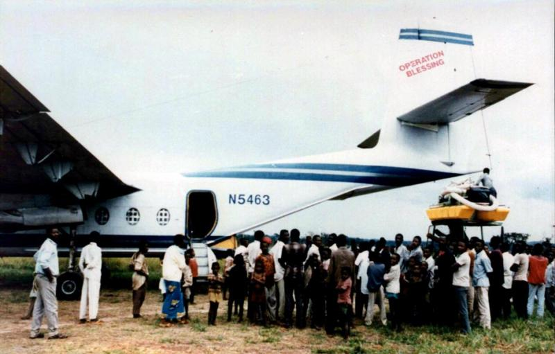 Curious villagers in Zaire (now Congo) watch a diamond-mining dredge being loaded onto a plane dispatched to Africa by Robertson's in-ternational charity, Operation Blessing, in the mid-1990s.